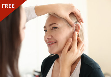 Audiologist fitting the hearing aid